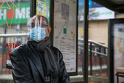 © Licensed to London News Pictures. 20/03/2021. London, UK. A man wearing a visor at a bus stop in north London. The UK government fears a rise in Covid-19 cases in the UK amid a new coronavirus surge across Europe, which has led to a number of European countries back into lockdown. Photo credit: Dinendra Haria/LNP