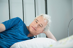 Portrait of mature man relaxing in bed, smiling
