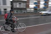 Een man fietst door de regen in Groningen.<br /> <br /> A man is cycling in the rain in Groningen.