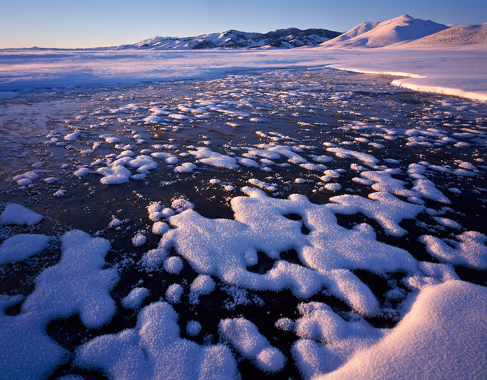 Open Edition includes all sizes Frozen spring on the Camas Prairie in Southwest Idaho has clumps of ice crystals creating a mosaic pattern in waters surface in the alpenglows last light of the day.
