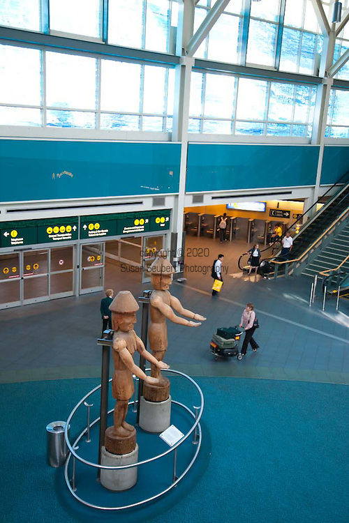 YVR, Vancouver, B.C. International Airport.  The interior design of the International Terminal was inspired by British Columbia's great outdoors and the art of the Northwest Coast that depicts British Columbia's native wildlife, mountains, rivers, forests, and aboriginal heritage.  In true Coast Salish tradition, two red cedar Welcome Figures stand tall at the entrance to the Arrivals Hall of the International Terminal. Carved by Susan A. Point of the Musqueam people, the figures stand at a height of approximately six meters (17 feet), and portray an inspiring welcome for all arriving passengers..Carved from the same log, one figure represents a male form and the other a female. Their carving style reflects the art of early coast Salish culture..Figures such as these were originally carved as house posts; however, the Welcome Figures in the International Terminal will remain as free-standing sculptures to silently, yet auspiciously, welcome passengers to Vancouver.