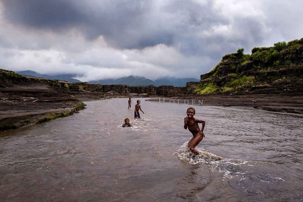 Ni-Vanuatu kids play in a volcanic river flowing near Yasur volcano.