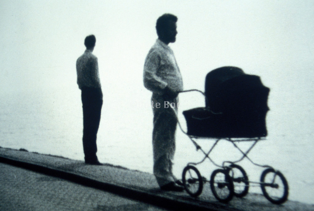 Two men with a baby carriage, one standing at a distance