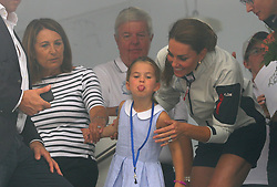The Duchess of Cambridge with Princess Charlotte and Carole Middleton (left) look through a window at the prize giving after the King's Cup regatta at Cowes on the Isle of Wight.