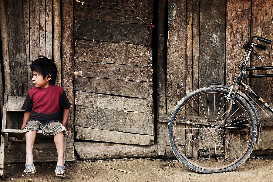 The son of a coca farmer sits outside his home in the upper valley of the Madre de Dios River in the Peruvian Amazon on September 3, 2005.