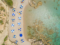 Aerial view of checkered parasols on the shore of Rhodes island, Greece.