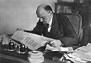 Vladimir Ilyich Lenin (Ulyanov 1870-1924) reading 'Pravda' 1918. Russian revolutionary.