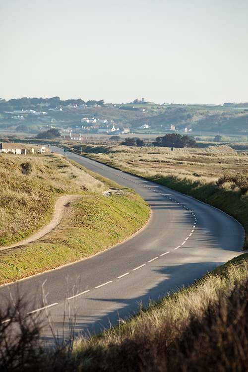 The Five Mile Road at St Ouen's Bay, surrounded by sand dunes and houses up on the hillside in Jersey, Channel Islands