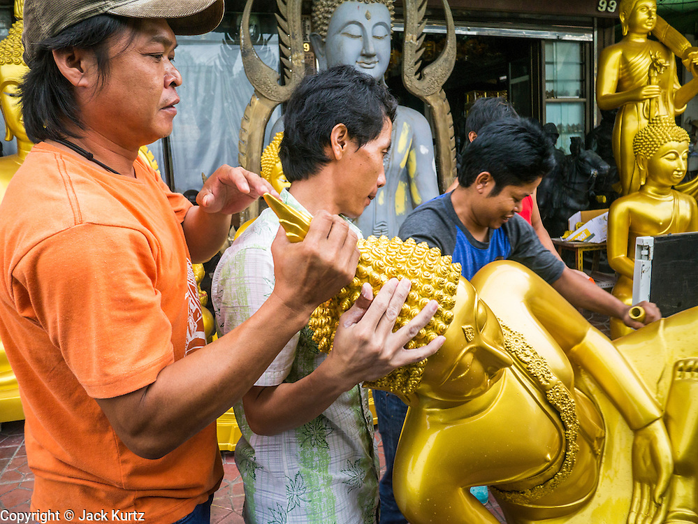 """12 NOVEMBER 2012 - BANGKOK, THAILAND:   Workers deliver a Buddha statue to shop on Bamrung Muang Street in Bangkok. Thanon Bamrung Muang (Thanon is Thai for Road or Street) is Bangkok's """"Street of Many Buddhas."""" Like many ancient cities, Bangkok was once a city of artisan's neighborhoods and Bamrung Muang Road, near Bangkok's present day city hall, was once the street where all the country's Buddha statues were made. Now they made in factories on the edge of Bangkok, but Bamrung Muang Road is still where the statues are sold. Once an elephant trail, it was one of the first streets paved in Bangkok. It is the largest center of Buddhist supplies in Thailand. Not just statues but also monk's robes, candles, alms bowls, and pre-configured alms baskets are for sale along both sides of the street.    PHOTO BY JACK KURTZ"""