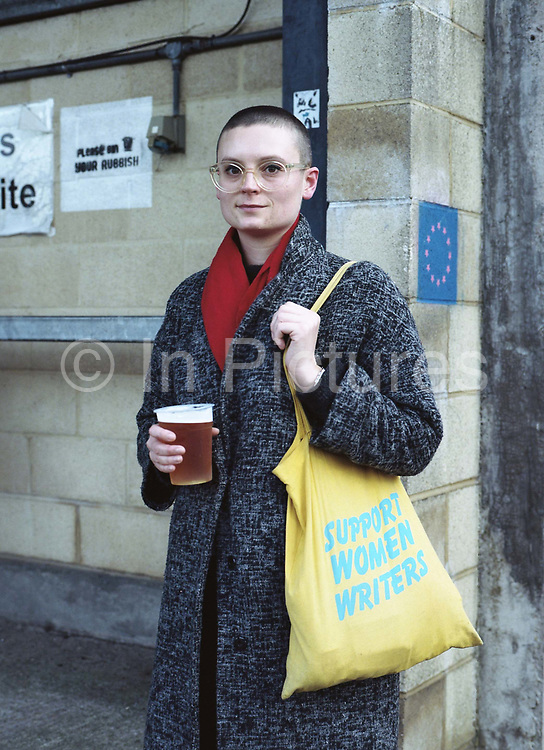 Gayle Lazda holds a pint of beer, wearing glasses and a red scarf, with a yellow tote bag saying 'Support Woman Writers' during the Dulwich Hamlet Vs Slough Town on the 29th December 2018 at Champion Hill in South London in the United Kingdom.