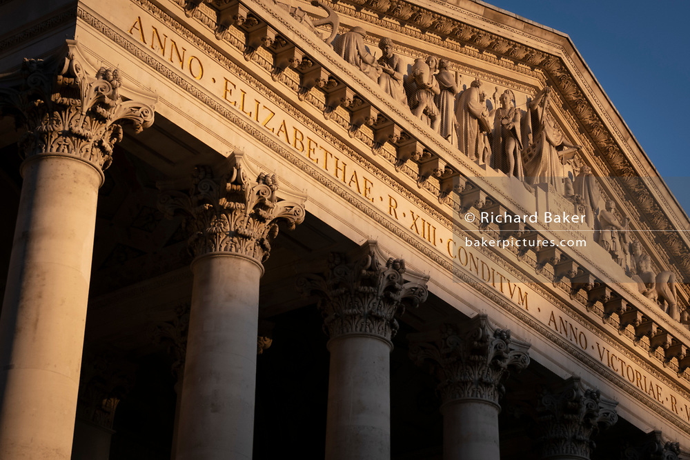 A sunlit detail of the friezes and Latin inscriptions on the pediment of the Royal Exchange in the City of London, the capital's financial district, on 27th February 2021, in London, England. At the top of Doric and Ionic columns with their ornate stonework, powerfully strong lintels cross, bearing the load of fine artistry and carvings which feature the design by Sir William Tite in 1842-1844 and opened in 1844 by Queen Victoria whose name is written in Latin (Victoriae R). It's the third building of the kind erected on the same site. The first Exchange erected in 1564-70 by sir Thomas Gresham but was destroyed in the great fire of 1666. It's successor, by Jarman, was also burned down in 1838. The present building is grade 1 listed and cost about £150,000.