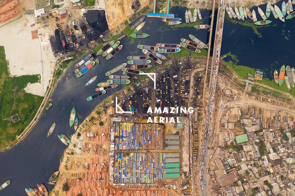 Aerial view of a busy wharf along Buriganga river with many sailing boats docked at shipyard in Keraniganj city, Dhaka, Bangladesh.