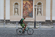 A cyclist rides past a mural and sculpture outside Cathedral of saint Nicholas in the Slovenian capital, Ljubljana, on 28th June 2018, in Ljubljana, Slovenia. Ljubljana is a small city with flat terrain and a good cycling infrastructure. It was featured at eighth on the Copenhagenize index listing the most bike-friendly cities in the world though bike theft is prevalent.