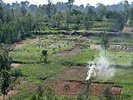 Rwanda- Smoke rises from a field in  a view of the countryside in the Southern Province, Rwanda.