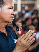 28 APRIL 2014 - BANGKOK, THAILAND: A man prays for Kamol Duangphasuk, 45, during the funeral for Kamol at Wat Samian Nari in Bangkok. Kamol was a popular poet who wrote under the pen name Mai Nueng Kor Kunthee. Kamol had been writing since the 1980s and was an outspoken critic of the 2006 coup that deposed Thaksin Shinawatra. After the 2010 military crackdown against the Red Shirts he went into temporary self imposed exile fearing for his safety. After he returned to Thailand he organized weekly protests against Thailand's Lese Majeste laws, which he said were being used to stifle dissent. Kamol was shot and murdered on April 23. The assailants are still at large but the murder is thought to be political.     PHOTO BY JACK KURTZ