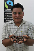 Justiniano Bol Junior, 26, Mopan Mayan cacao grower and TCGA's field extension officer, holds Cacao beans at the San Antonio office. Justiniano has been TCGA's field extension officer at the San Antonio branch for four years and is the son of Justiniano and Florentina Bol, both life-long cacao growers and long term TCGA members. Justiniano Junior plans to continue growing cacao in the Toledo region as his family has for generations. Toledo Cacao Growers' Association (TCGA), San Antonio, Toledo, Belize. January 25, 2013.