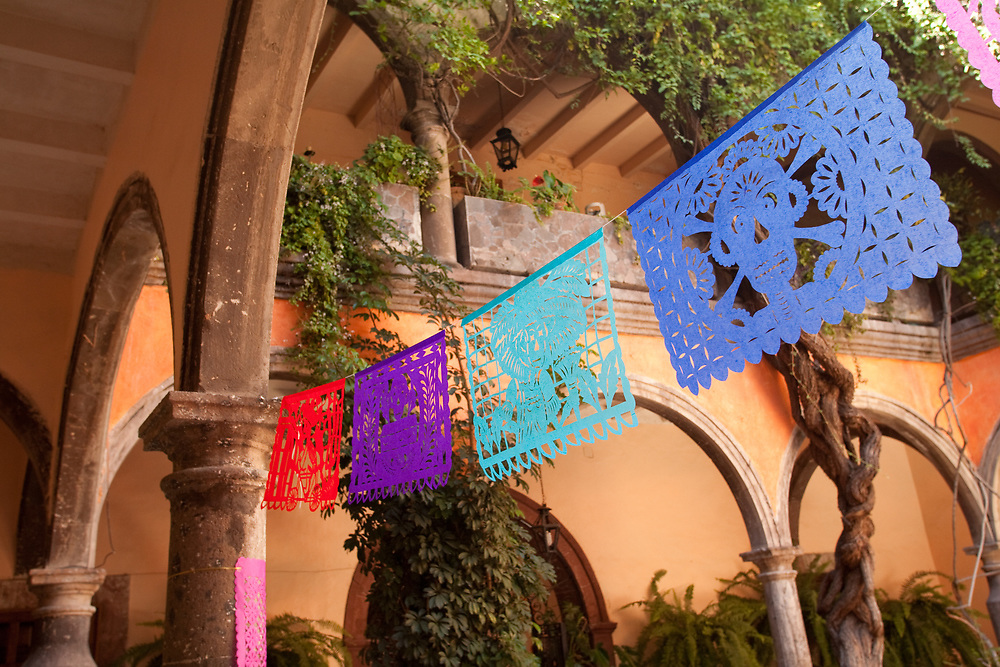 North America, Mexico, San Miguel de Allende, banner of tissue paper flags (papel picado) hanging between arches in traditional courtyard during Day of the Dead  celebration, also known as Dios de los Muertos.
