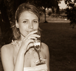 bride at wedding drinking a glass of champagne