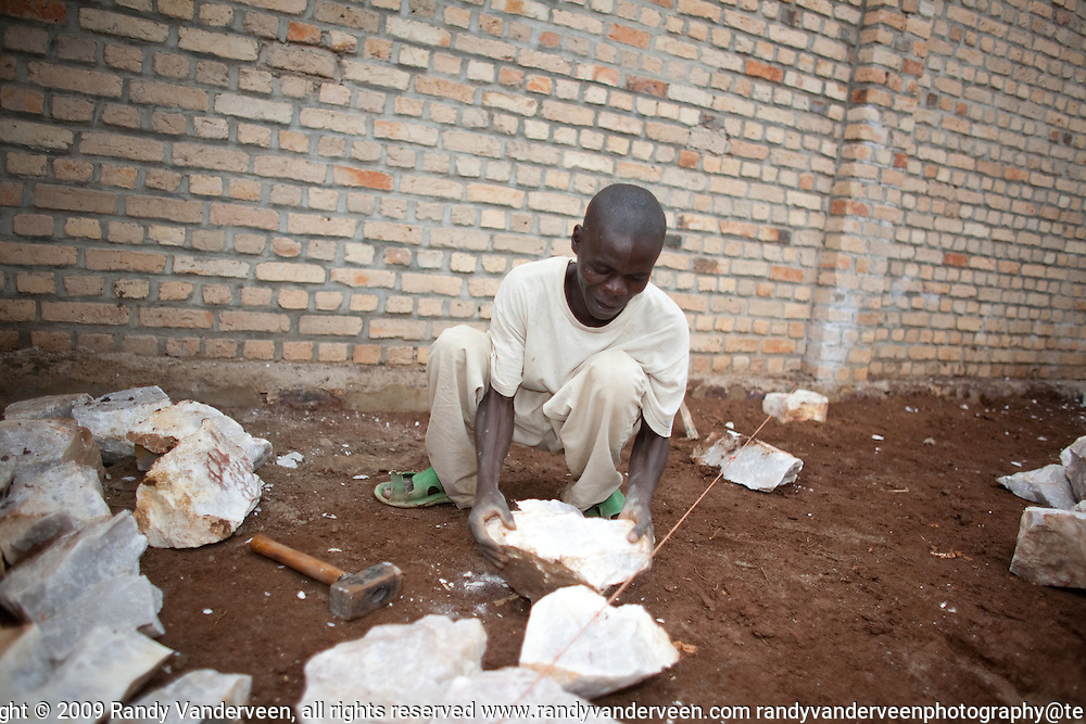 Photo Randy Vanderveen.Nyrusange, Rwanda.A worker breaks stones for the floor of a new school class room under construction at the Gary Scheer school in rural south Rwanda. Classrooms at schools in the nation have to be all be built of fired-brick as part of the country's Vision 2020 mandate.