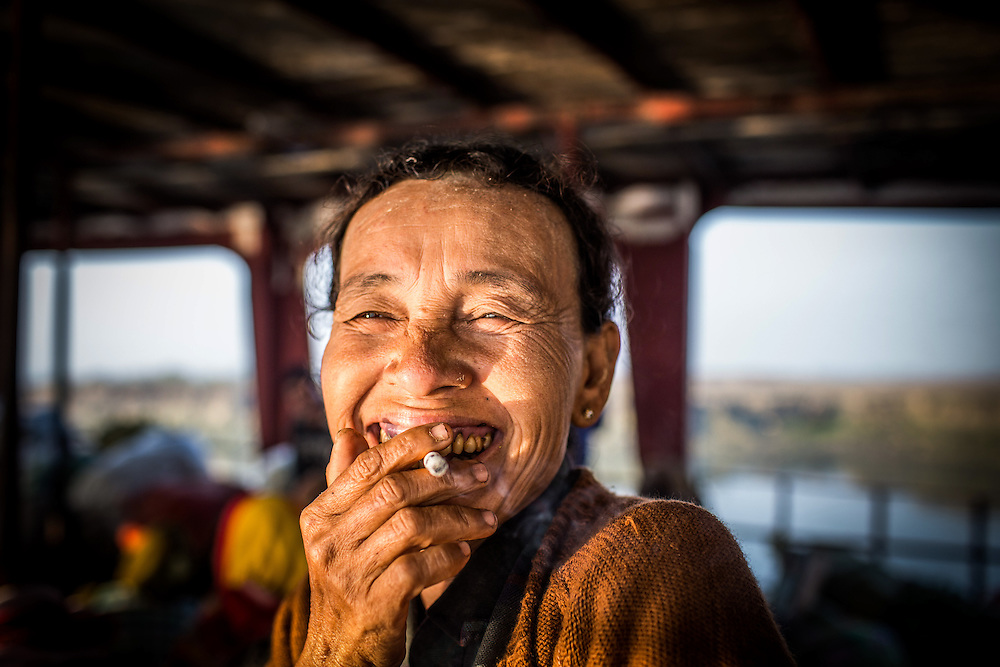A woman on the ferry from Mrauk U to Sittwe in the Rakhine State of Myanmar smiles as a take her portrait.