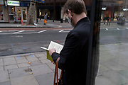 A man reads the pages of a music notation book on Charing Cross Road, on 30th October 2020, in London, England.