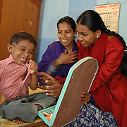 Arathi (23) is the CBR worker. She suffered from polio as a child and now works for APD after completing a 14 month course in physiotherapy..Here helping Shaifula (6), a mentally retarded boy, to learn how to put on his clothes while his mother watches with joy.