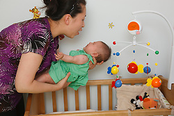 Chinese mother putting baby to bed