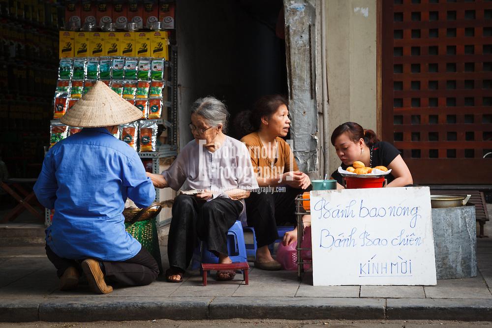 15/04/2013 - Hanoi, Vietnam. Vietnamese women in the Old Quarter of Hanoi selling Banh Bao (steamed dumplings). Photo by Rob Arnold