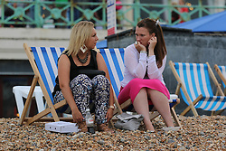 © Licensed to London News Pictures. 14/06/2014. Brighton, UK. Two girls relaxing on Brighton beach. Cloudy and the occasional shower hasn't stopped people from visiting Brighton and spending the day at the beach. Photo credit : Hugo Michiels/LNP