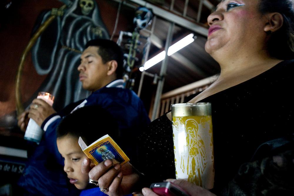 Sante Muerte devotees prays in front of a popular shrine in Tipito in Mexico City.