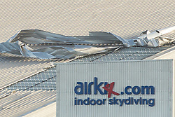 © Licensed to London News Pictures . 05/12/2013 . Manchester , UK . Sheets of corrugated metal are blown off the roof of the Chill Factore indoor ski slope in Trafford , Manchester as high winds cause a lorry to overturn on the adjacent M60 motorway . Sheets of the metal were observed flying from the roof and towards the motorway as high winds cause damage across the UK . Photo credit : Joel Goodman/LNP