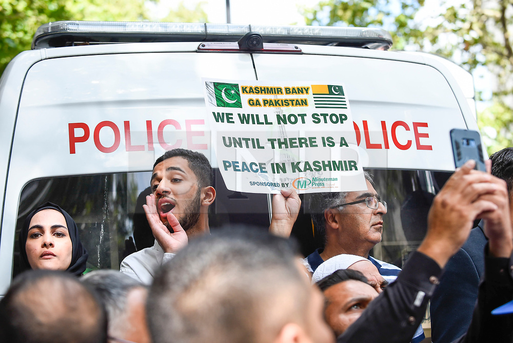 © Licensed to London News Pictures. 15/08/2019. LONDON, UK.  People next to a police van as thousands of protesters, many waving Pakistani and Kashmiri flags, gather outside the Indian High Commission in Aldwych, on what they are calling Black Day, to stand in solidarity with the people of Kashmir.  Indian Prime Minister Narendra Modi delivered an Independence Day speech highlighting his decision to remove the special rights of Kashmir as an autonomous region.  Photo credit: Stephen Chung/LNP