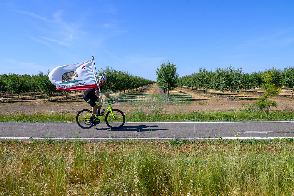 May 12, 2019 - Sacramento, CA, USA - Racing fans rides his bike carrying the California flag during the Amgen Tour of California on Sunday, May 12, 2019 in Davis. (Credit Image: © Paul Kitagaki Jr./ZUMA Wire)