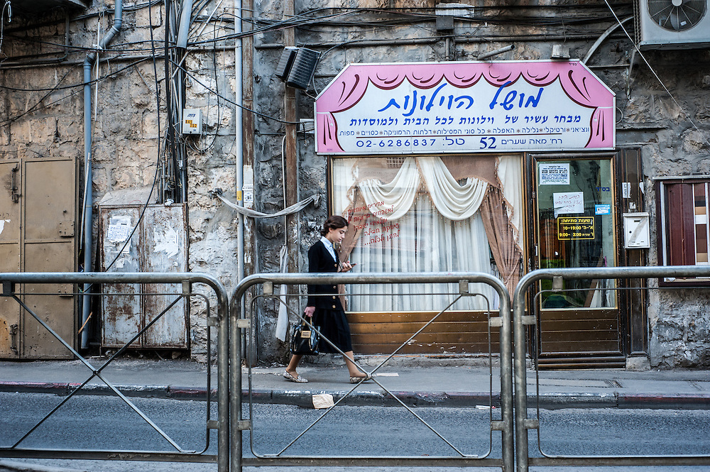 A young woman walks down the street while looking at her cell phone in the Mea Sharim neighborhood of Jerusalem