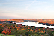 Keuka Lake, New York.  Vineyards and forestland cover the slopes on either side of Keuka Lake in the Finger Lakes of New York State.  Autumn colors were taking over and there was a chill in the air at a high point above the lake.  As evening shadows lengthened up the mountains, Bluff Point, splitting the lake in half, lit up with the setting sun.