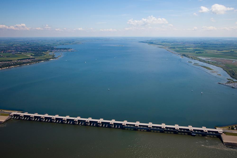 Nederland, Zuid-Holland, Haringvliet, 12-06-2009; Haringvlietsluizen en Haringvlietdam, tussen Voorne-Putten en Goeree-Overflakkee. Gezien naar  het zuidoosten, het Haringvliet landinwaarts. De sluizen, onderdeel van de Deltawerken, zijn spuisluizen en zorgen er voor dat het zoete water uit het Haringvlie zoals aangevoerd door Maas en Rijn geloosd kan worden. In het kader van modern natuurbeheer  ('getemd getij') gaan de sluizen tegenwoordig bij eb én vloed beperkt open rechts op de foto), om de getijden hun enigszins terug te laten komen in het estuarium .Dam and sluices between islands Voorne-Putten en Goeree-Overflakkee (bottom); the sluices are for draining water coming from the rivers Rhine and Maas (Meuse) from the natural bassin (right) to the North sea (left). Modern ecolical insight has led to opening the sluices semi-permanently, resulting in the estuary function of the Haringvliet patially being restored.Swart collectie, luchtfoto (25 procent toeslag); Swart Collection, aerial photo (additional fee required).foto Siebe Swart / photo Siebe Swart