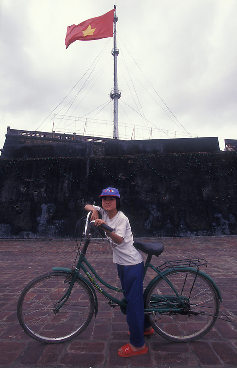 Hue girl with her bicycle, Flag tower, Hue citadel.