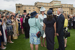 The Duchess of Cambridge (centre) talks to guests during a garden party at Buckingham Palace in London.