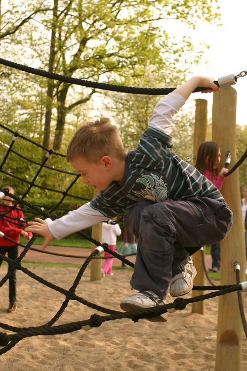 Young boy playing on rope bridge in playground.