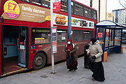 Two women having to take the bus during the third national coronavirus lockdown in Birmingham city centre, which is empty apart from a few people on 12th January 2021 in Birmingham, United Kingdom. Following the recent surge in cases including the new variant of Covid-19, this nationwide lockdown, which is an effective Tier Five, came into operation yesterday, with all citizens to follow the message to stay at home, protect the NHS and save lives.