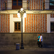 People walking past tiled wall at night in Puebla