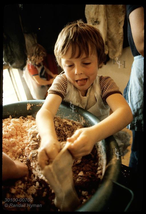 Boy crams lamb fat & blood into bag of intestinal skin,a national delicacy called 'slatur'; Myvatn Iceland