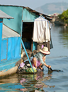 A girl doing laundry in the water of the Tonlé Sap lake, Cambodia. She lives in one of the floating village communities on the massive lake.