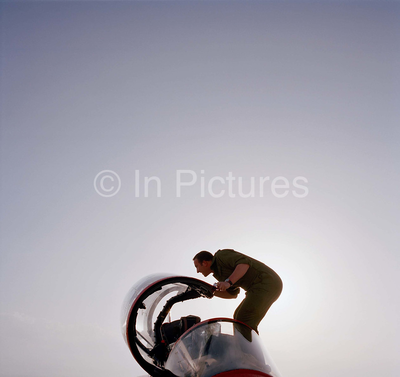 Darren Budziszewski is a Junior Technician engineer in the elite 'Red Arrows', Britain's prestigious Royal Air Force aerobatic team. He is seen carefully standing in the cockpit of a Hawk jet closely inspecting the Plexiglass canopy for smears and scratches. Stooping at the open surface while keeping back flat and his knees bent, its posture that the RAF teaches its employees. Darren polishes the aircraft before its pilot emerges from the building at RAF Akrotiri, Cyprus. The Red Arrows ground crew take enormous pride in their role as supporting the team whose air displays are known around the world, cleaning the red airplanes on their day off, so particular are they. The image is backlit and both canopy and man are bottom-weighted to allow us to see space and sky. Specialists like Darren outnumber the pilots 8:1 and without them, the Red Arrows couldn't fly.