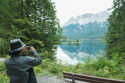 Rear view of tourist taking picture with camera at Eibsee lake, Bavaria, Germany