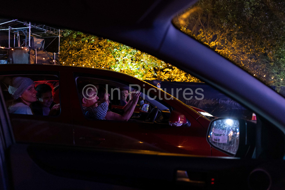 From inside their cars, opera fans applaud the performance of Puccini's La bohème, performed by members of  English National Opera (ENO) as a drive-in (ENO Drive and Live) at Alexandra Palace, on 18th September 2020, in London, England. This is ENO's first public performance since the closure of their West End Colisseum home venue, because of the Coronavirus pandemic lockdown in March. This is Europe's first live drive-in opera production that audiences can safely experience from their cars and ENO's first public performance since the closure of their West End Colisseum home venue, because of the Coronavirus pandemic lockdown in March. As per the latest government advice. Each bubbled group consists of; 34 members of the ENO Orchestra, 20 ENO Chorus members and 8 principals. Each bubble has its own individual crew to oversee their rehearsals and performances.
