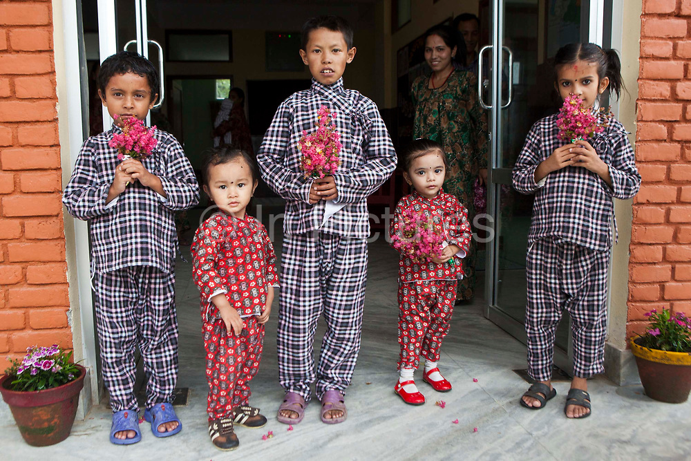 Nepalese children stand outside the doorway of the Friends of Needy Children Nutritional Rehabilitation Home welcoming visitors in Kathmandu, Nepal.  They are wearing hospital pajamas and holding pink flowers. The centre has recently been built.  It treats malnourished children and provides education to mothers about nutrition and childcare.