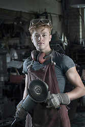 Portrait of trainee blacksmith with angle grinder at workshop, Bavaria, Germany