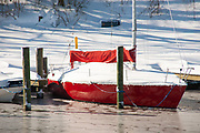 Red-hulled sailboat covered in snow