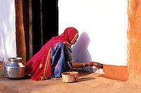 Inde. Rajasthan. Village dans les environs de Barmer. Une femme peint  sa maison pour la fête de nouvel année. (Diwali) // India. Rajasthan. Village near Barmer. Woman painting her house for new year festival (Diwali).